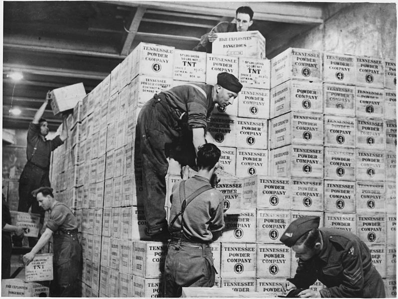 Cases of TNT shipped from the USA under Lend-Lease are stacked in an underground ammunition dump, somewhere in England [Public domain, wikimedia]