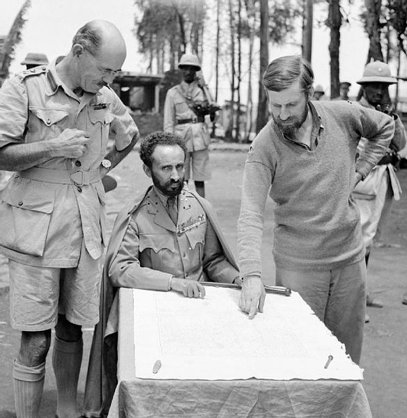 Haile Selassie glances up from table as Orde Wingate points out a feature on the map, 1941 [Public domain, Imperial War Museum/wiki]