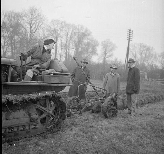 British 'land girl' demonstrates a Chicago-built Lend-Lease tractor to visiting American farmers, somewhere in Buckinghamshire, England [Public domain, IWM/wiki]