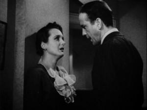 Crusty private eye Sam Spade (Humphrey Bogart) confronts femme fatale Brigid O'Shaughnessy (Mary Astor) in the movie 'The Maltese Falcon' [Public domain, wiki]