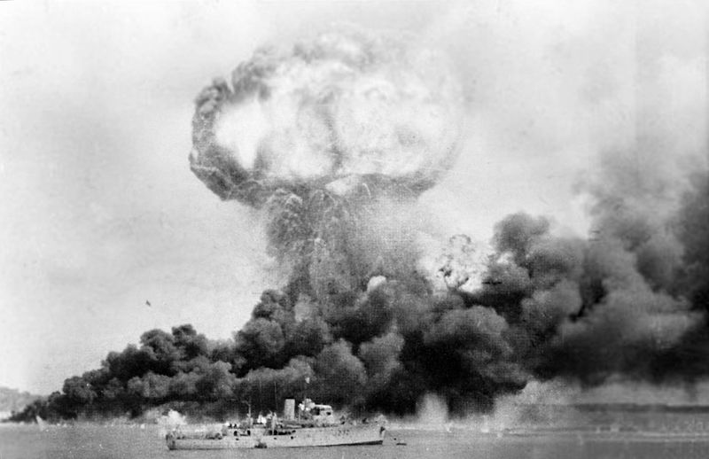 Oil storage tanks ablaze after the 19 February 1942 air raid on Darwin; HMAS Deloraine is in the foreground [Public domain, Australian War Memorial]