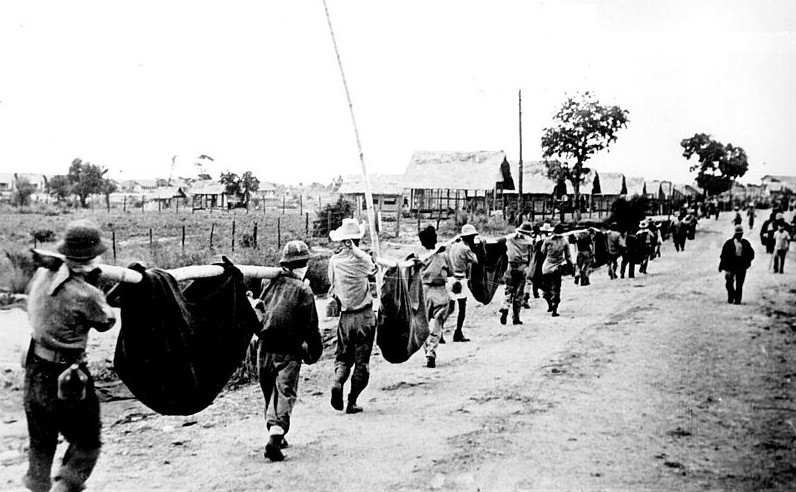 American prisoners carry comrades unable to walk; picture taken by a Japanese photographer during the march from Bataan, Philippines 1942 [Public domain , wiki]