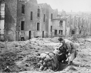 A man inspects the propulsion unit of a V-2 rocket that has devastated a neighbourhood in Limehouse, East London, March 1945 [Public domain]