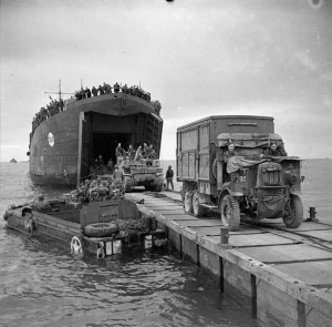 British troops bring equipment ashore at Anzio; an American DUKW is floating alongside the jetty; January 1944 [Public domain]