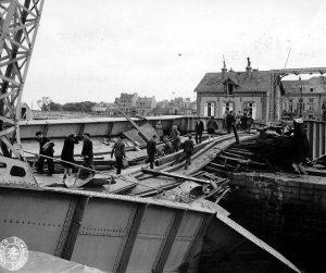 Civilians cross a wrecked bridge in Cherbourg, 1944 [Public domain]