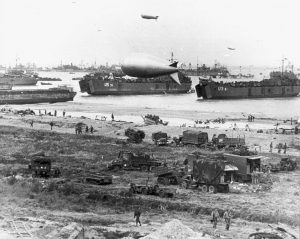 US Navy LSTs deliver vehicles to a beach in Normandy, likely D-Day +1 [Public domain]