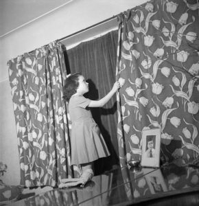 Doreen Buckner draws the curtains in her family's London home to comply with the nightly 'Blackout' [Public domain]